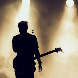 Rock band performs on stage. Guitarist plays solo. silhouette of guitar player in action on stage behind lights.