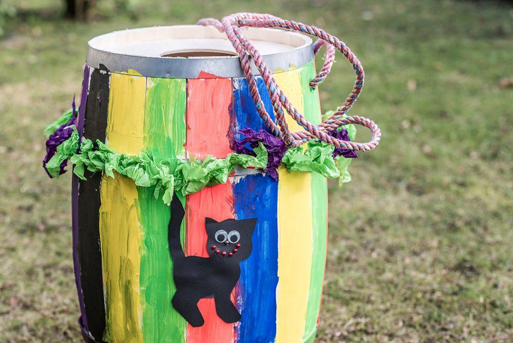 tønne malt i ulike farger med en svart katt i papir utenpå